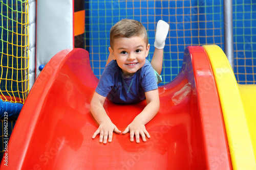 Photo  Little boy riding on slide in entertainment center