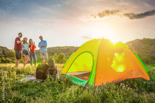 Poster Camping Camping gear and group of young people in wilderness