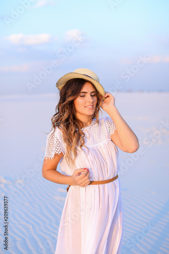 Fotografía  Young nice female person wearing white dress and hat standing on sand in monophonic background