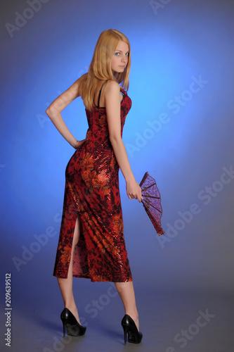 Foto op Plexiglas womenART beautiful young blonde in a red dress with a fan in the studio