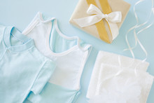 New, Light Blue Baby Clothes And Box With White Ribbon On The Pastel Blue Table. Soft Colors. Giving Or Receiving Gifts At Baby Shower Party.