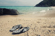 Summer vacation concept,yellow striped sandals on sea beach with vintage tone.