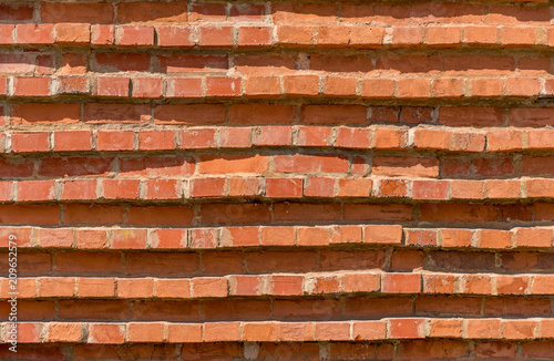 Foto op Plexiglas Wand Uneven wall of red bricks as background