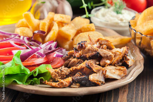 Greek gyros dish with french fries and vegetables