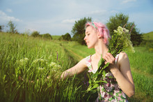 Portrait Of A Happy Young Cute Girl With Multi-colored Hair Collects Flowers Next To A Country Road At Sunset. The Concept Of Human Harmony With The Nature Of Spring And Happiness