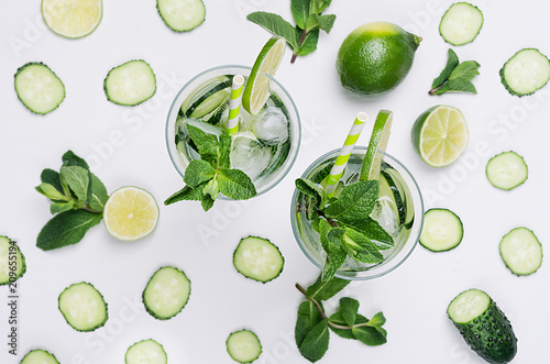 Keuken foto achterwand Groenten Summer fresh background - cold natural refreshing cocktail with slices cucumber, lime, mint, ice, straw on white wood plank, top view.