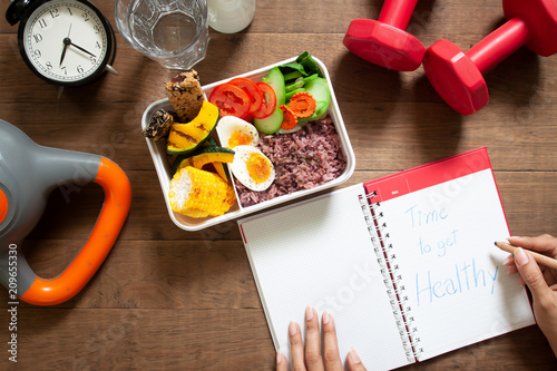 Fotografia  Healthy concept with nutrion food in lunch box and fitness equipments with woman