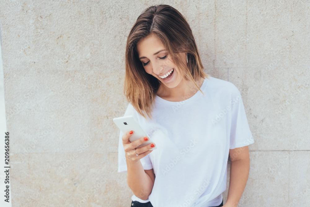 Fototapety, obrazy: junge frau lacht und schaut auf ihr smartphone