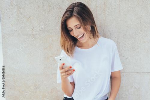 Obraz na plátně  junge frau lacht und schaut auf ihr smartphone