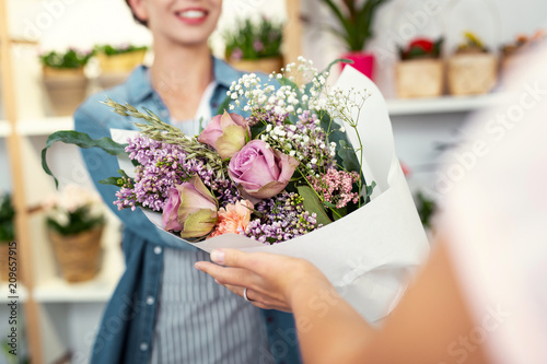 Floristic masterpiece. Selective focus of a big beautiful bouquet being in given to a customer of the flower shop