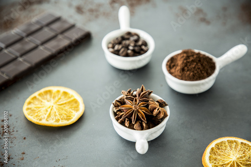 In de dag Aromatische Cloves, coffee and cinnamon set on a table next to a bar chocolate and orange slices