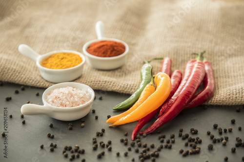 Fotobehang Aromatische Chili peppers, salt, turmeric powder and red pepper powder on a table with black pepper strewn around