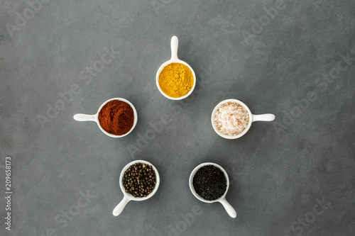 In de dag Aromatische Top view of bowls with spices arranged in a circle on a grey background