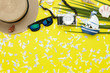 Table top view aerial image of items to travel summer holiday background concept.Flat lay essentials accessories for travel to beach trip.Fashion sun glasses with camera & hat on green coconut leaf.