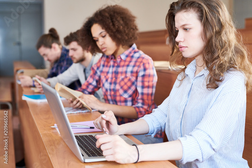 Serious concentrated student girl with curly hair sitting at