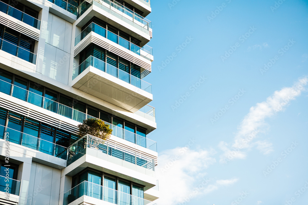 Fototapety, obrazy: The corner of the building with many windows against the blue sky