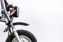 Close Up Of Headlight And Front Wheel On Vintage Motorcycle. Custom Scrambler Motocross. Retro Motorbike On White Background. Blank Copy Space For Text.