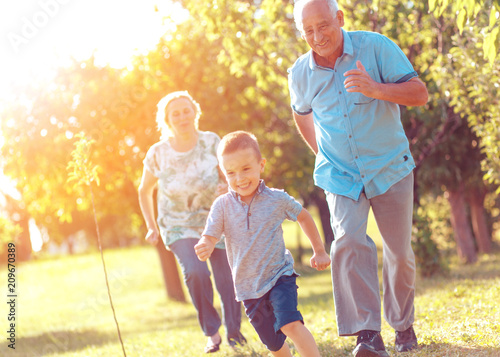 Obraz Grandparents with grandson enjoying time together in park. - fototapety do salonu
