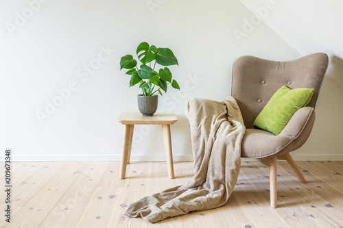 Fotografía Beige armchair with a green pillow, blanket and a wooden table with a potted plant, fruit salad tree (Monstera deliciosa)