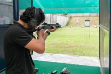 Man Wear Ear Plug Aiming Shotgun At Target In Shooting Range. Men Practicing Fire Pistol Shooting.