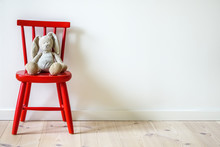 Children's Furniture. Small Red Wooden Chair With Stuffed Bunny Rabbit. White Blank Wall In Simple Interior With Copy Space.