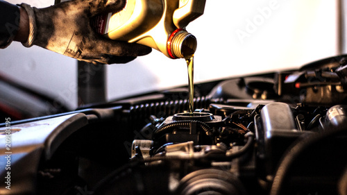 Mechanic fills up the car engine with engine oil