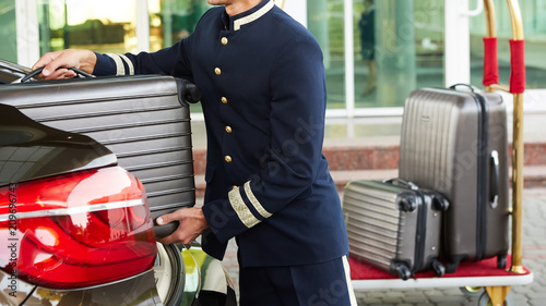 Cuadros en Lienzo Bellboy taking baggage of guest from thee car to his room
