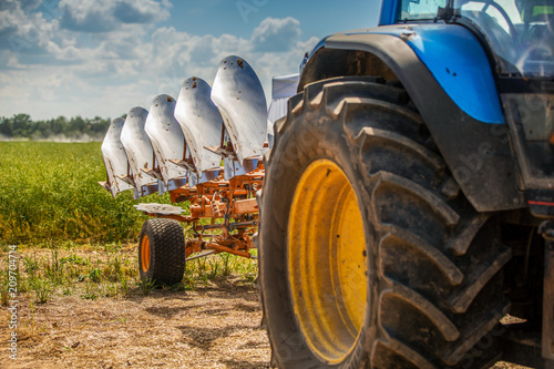 Fotografía tractor with plough beside the field