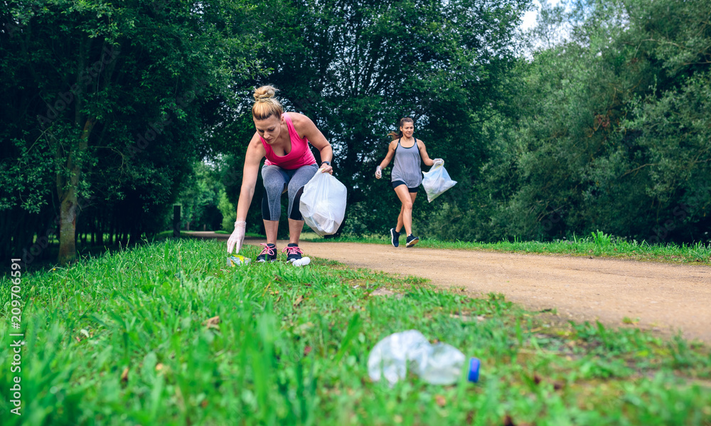 Fototapeta Two girls picking up trash while plogging outdoors