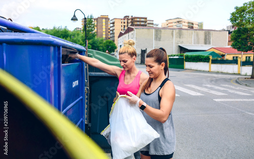 Fototapeta Two girls throwing garbage to recycling dumpster after plogging