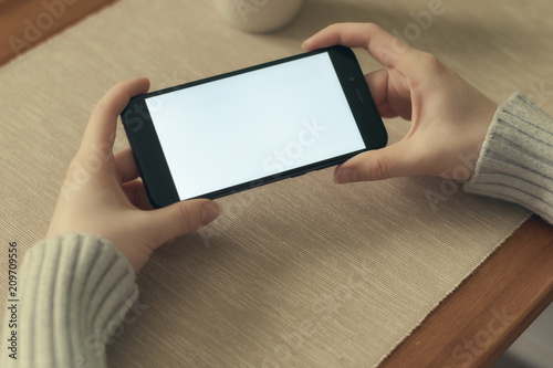 Girl watching video or play game on mobile phone in horizontal position. Isolated screen for app mockup, presentation.