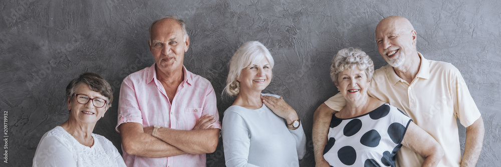 Fototapeta A panorama portrait of  a group of happy elderly men and women in colorful summer clothes laughing and posing on a dark background
