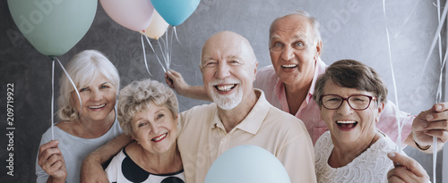 Obraz A group of happy, senior friends holding colorful balloons while posing at a party and celebrating birthday together. - fototapety do salonu