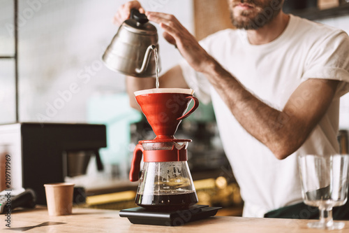 Fotografering Close up photo of barista at bar counter preparing coffee in pour over and hario