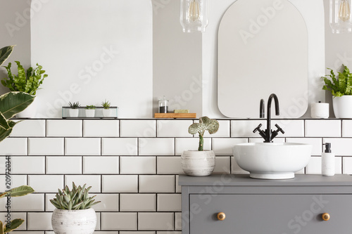 Fotografia  Real photo of a sink on a cupbaord in a bathroom interior with tiles, mirror and
