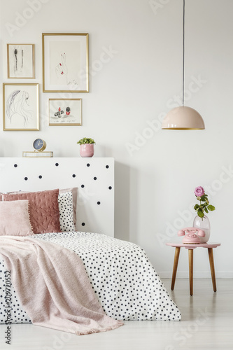 Fotografía  Pink, old-fashioned phone on a wooden side table and a pendant lamp in a serene