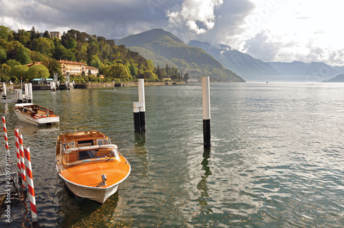View of Lake Como in a cloudy day with motorboat and harbor in Bellagio, a charming village between the lake and the mountains of Alps Wallpaper Mural