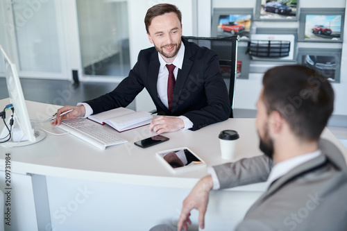 Portrait of bearded handsome sales manager talking to client while sitting at desk in car showroom