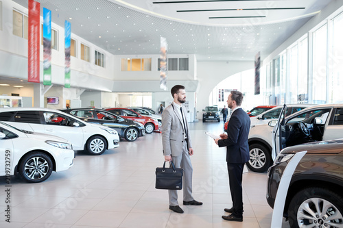 Obraz na plátne Full length portrait of handsome car salesman talking to customer in luxury show