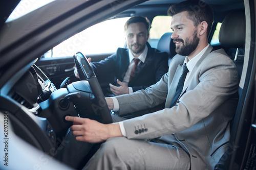 Fotografie, Obraz  Side view portrait of mature bearded businessman sitting inside brand new car in