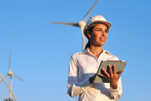 An Engineer Controls The Functioning Of Wind Turbines That Run Thanks To The Force Of The Wind And Generate Electricity Sustainably To The Planet. Concept Of: Renewable Energy, Love For Nature