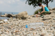 Plastic bottle dumped on the coastal strip with blurry woman picking up the garbage on the background.