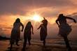 Silhouette of Happy girls running together on sunset sea beach. Summer holiday concept. Cinema film tone with grain.