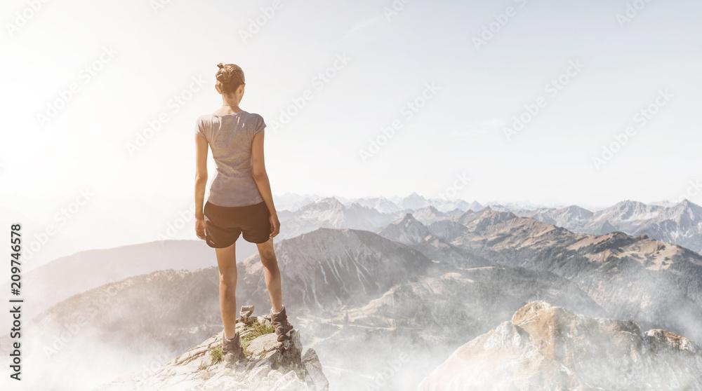 Fototapety, obrazy: Frau steht auf einem Berggipfel am Morgen