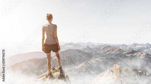 Fototapeta Frau steht auf einem Berggipfel am Morgen obraz