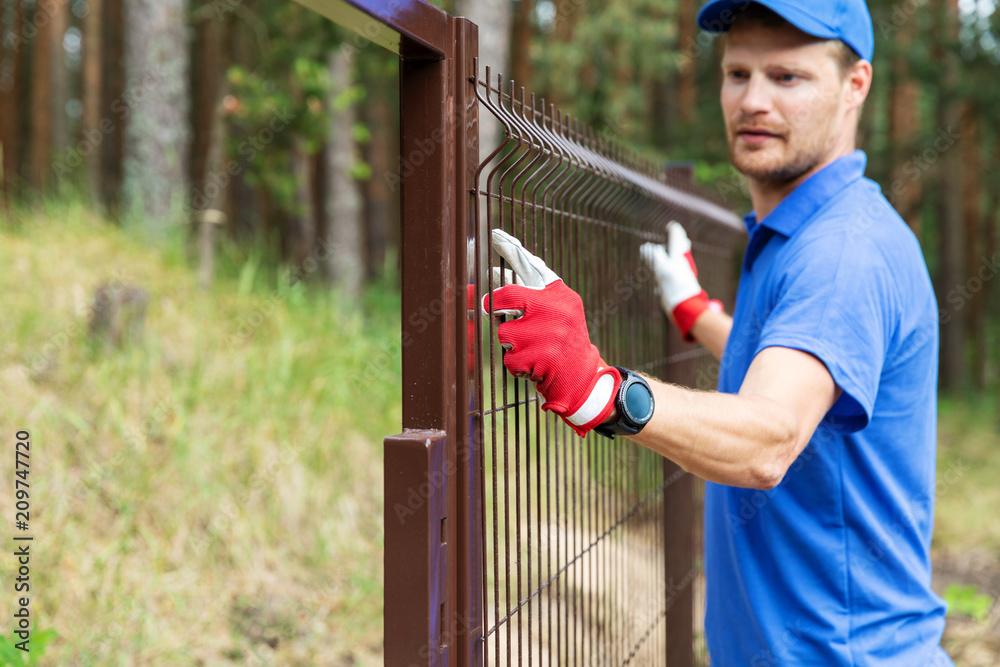 Fototapeta worker installing welded metal mesh fence