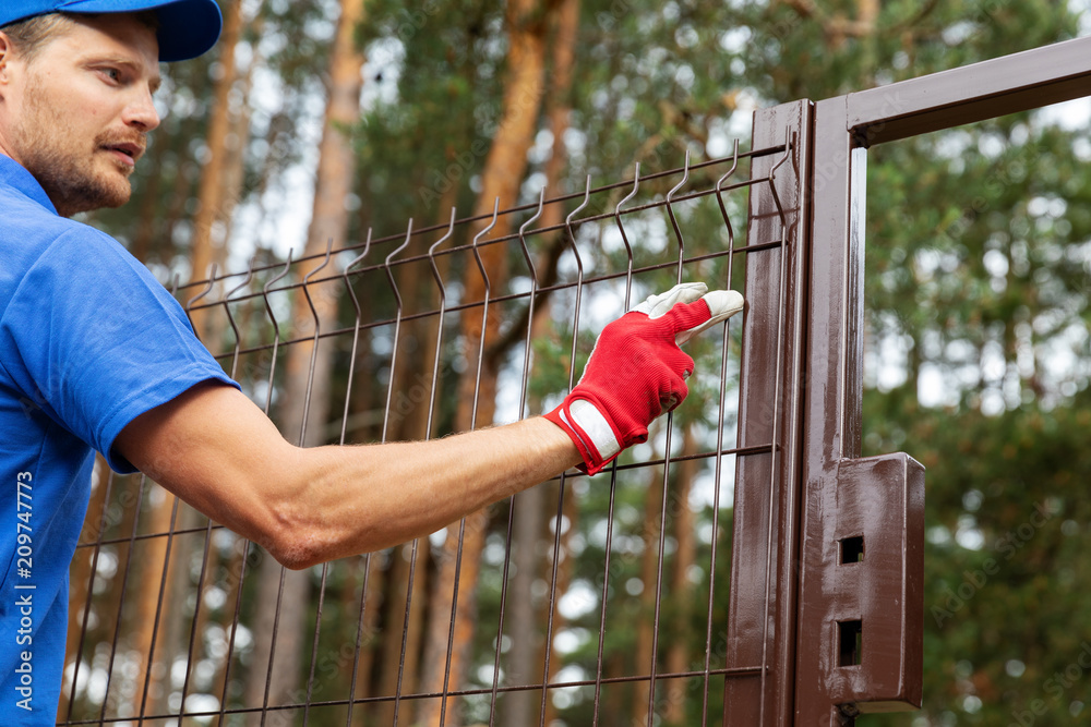 Fototapeta territory enclosure - worker installing metal fence