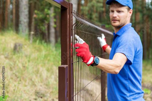 worker installing welded metal mesh fence Tableau sur Toile