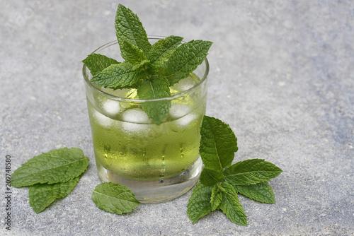 Fotografia  Ein Glas mit einer klaren grünen Flüssigkeit wird mit Eiswürfeln gekühlt und ist beschlagen