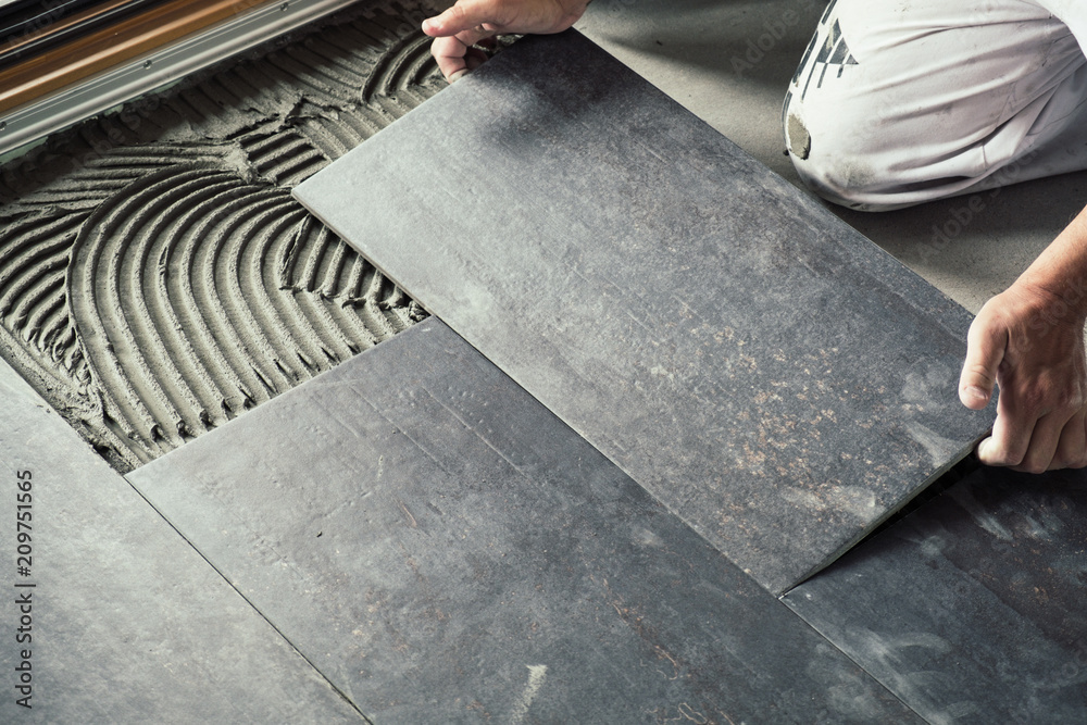 Fototapeta Worker placing ceramic floor tiles on adhesive surface
